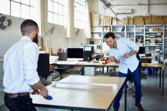 Employés jouant au tennis de table au bureau